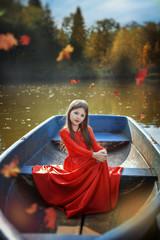 Девочка-цыганка плывет в лодке по озеру осенью
