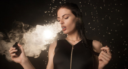 Young beautiful woman vaping e-cigarette in rain. Water flowing on woman face.