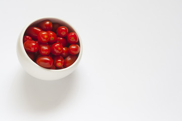 Some red plum tomatoes in a round white bowl on a white background