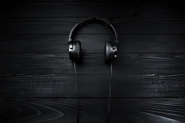 Black headphones on black wooden dark background.