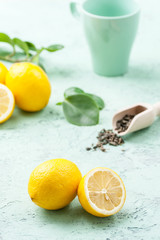 Ripe lemons, tea leaves and a cup on a mint-blue background..