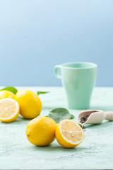 Ripe lemons and a cup of tea on a mint-blue background..