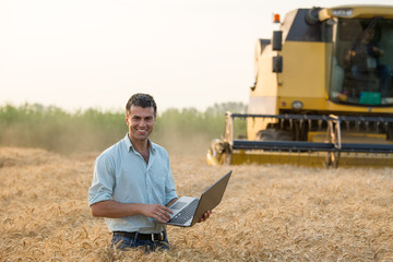 Farmer with laptop in field during harvest