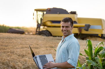 Engineer with laptop with combine harvester