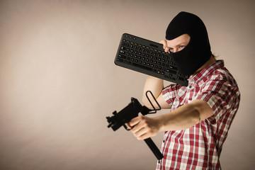 Man in balaclava holding keyboard and gun