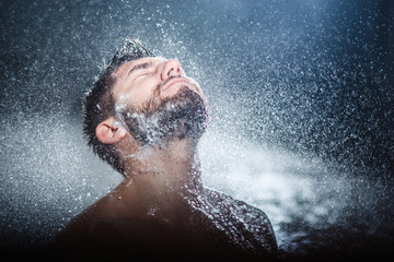 Headshot of a handsome fashionable young man taking shower, with water splashes all over
