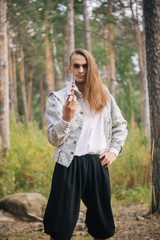 Sexy long-haired man with a pipe in his hands, in the woods. In a beautiful, ancient jacket with patterns and a white shirt. Fantasy.