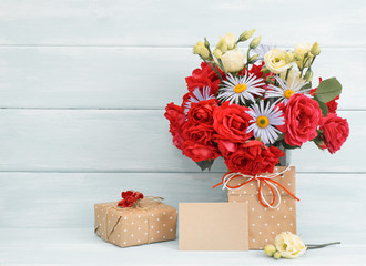 Roses and daisy bouquet, greeting card with gifts on wooden background in Shabby Chic style. Celebratory interior.