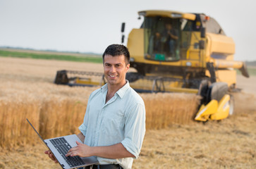 Engineer with laptop and combine harvester