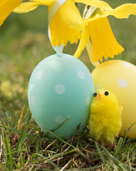 Vertical image: symbols of Easter festive: yellow little chick and Easter eggs are on green grass in a spring garden.