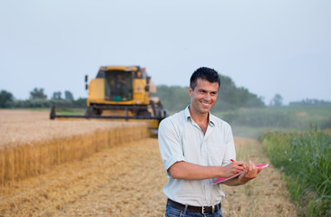 Engineer with notebook and combine harvester