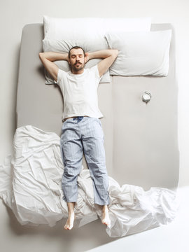 Top view photo of young man sleeping in a big white bed
