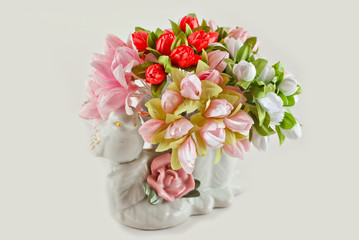 Multicolored artificial flowers on a white background