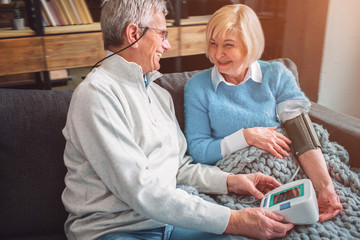 A picutre of happy old couple that like to be together. THe woman is measuring her blood pressure. The man is sitting besides her. They look lovely.