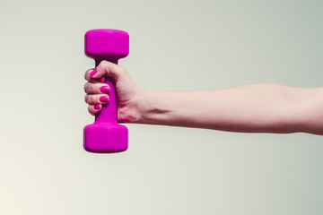 female lifting magenta colored dumbbell against teal background