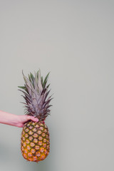 woman holding pineapple in hand against solid colored background