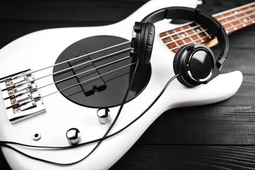 Black headphones and white bass guitar on the black wooden background.