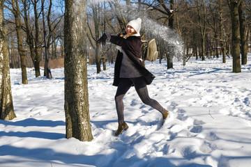 young beautiful girl playing snowballs