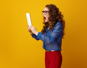 modern shocked woman isolated on yellow using tablet PC