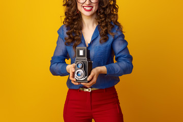 happy young woman isolated on yellow with retro photo camera