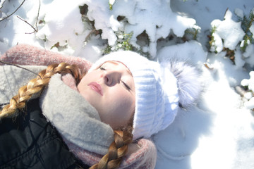 A young woman is lying in snow.
