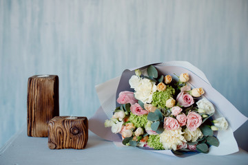 Modern bouquet of delicate pink roses in kraft paper lies on pedestal