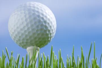 Golf ball on a tee isolated on a blue sky