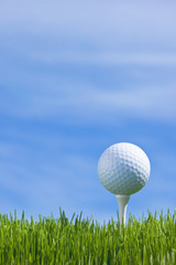 Golf ball on a tee isolated on a blue sky (vertical)