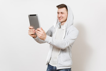 Young handsome smiling man in blue jeans, t-shirt and light sweatshirt with hood with headphones photographs himself on tablet pc computer isolated on white background. Concept of technology
