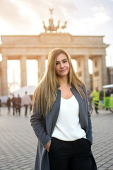 Portrait of beautiful young woman standing in front of Brandenburg Gate in Berlin, Germany.