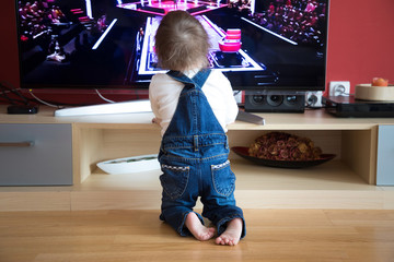 Baby boy watching TV at home living room