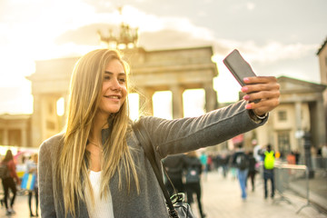 Beautiful blond girl taking selfie in front of Brandenburg Gate in the city of Berlin, Germany.