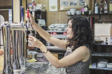 waitress serving beer in bar