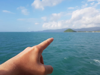 Photo of hand pointing finger into distance of sea coast, cloudy sky