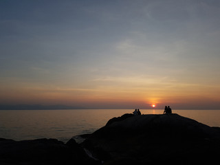 Photo of hill with seated people at sunset on seashore