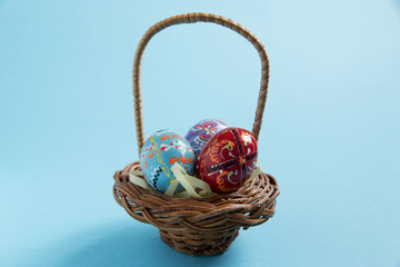 easter eggs painted in a basket on a blue background