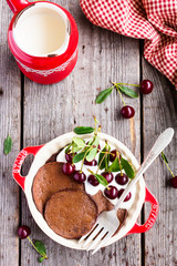 Chocolate pancakes with vanilla cream and ripe cherry in a plate on a wooden table, top view. Breakfast food. Morning style. Healthy and organic food option.