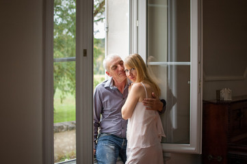 Senior Man Hugging His Young Blond Wife near the Window. Woman Looking at the Camera. Psychology of Relations Concept.