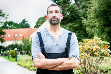 handsome man in dungarees standing outside