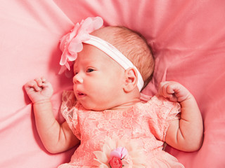 Newborn baby girl in pink dress and hat, lies on pink bed
