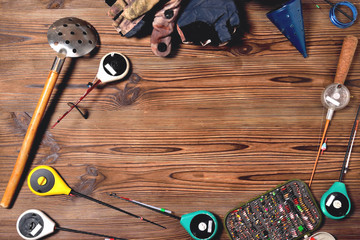 accessories for winter fishing on a brown wooden background, place for an inscription