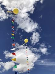 Zwei gelbe Ballons vor blauem Wolkenhimmel