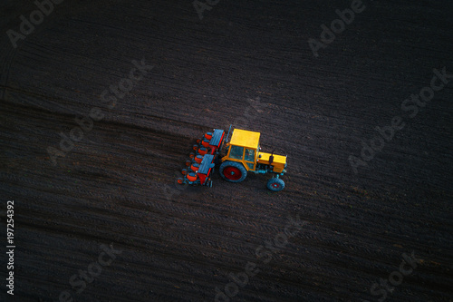 Wall mural Aerial drone view of tractor working on the harvest field