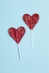 the red Lollipop candy in heart shape on dark blue background.