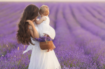 Happy beautiful mother and cute little daughter have fun in aroma lavender fields. Family holiday in summer day.
