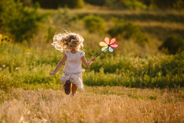 Cute little girl playing in the summer field of wheat Wall mural