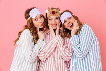 Three beautiful young girls 20s wearing colorful striped pyjamas and sleeping masks having fun during girlish sleepover, isolated over pink background