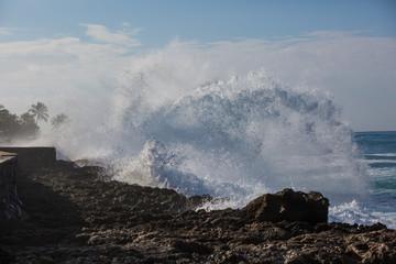 Tropical beach break, ocean wave crushing stone coastline, water splashes