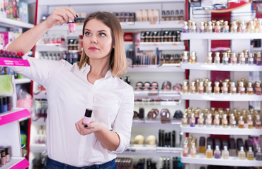 Woman looking for new color of nail varnish