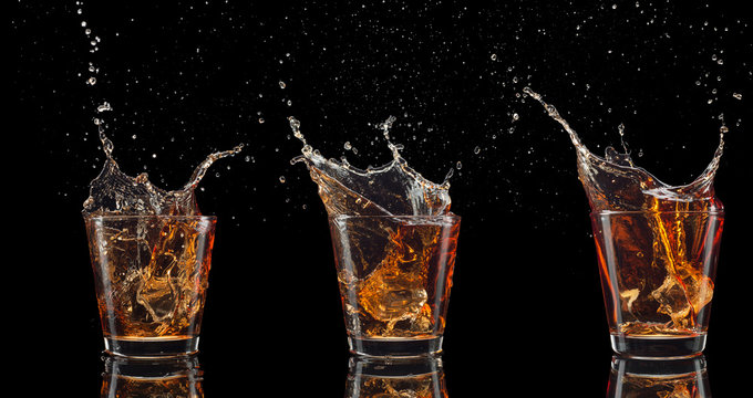 set of whiskey shots with splash isolated on black background